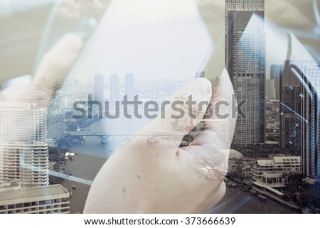 concept image of Business & technology, Using digital tablet double exposure and and cityscape background.  - stock photo