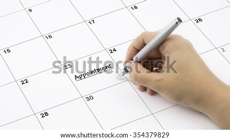 Concept image of calendar with a woman hand writing. Words Appointment written on calendar to remind you an important appointment.