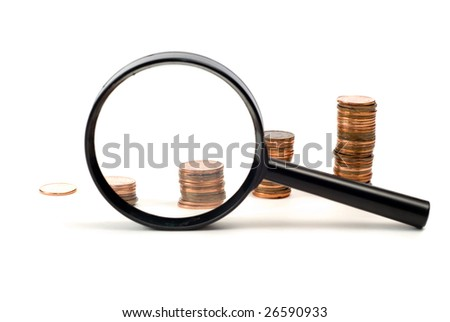 Concept image of examining investments using stacks of pennies and a magnifying glass