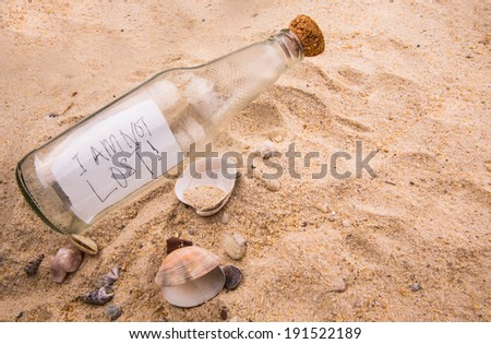 Concept image of I AM NOT LOST message written on a piece of paper in a glass bottle on beach sand