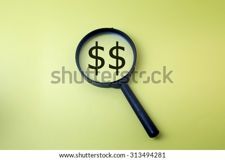 Concept image of magnifying glass showing the money symbol