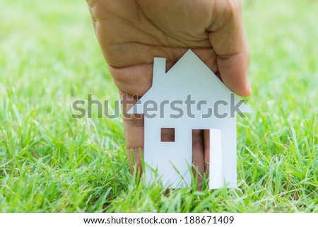 concept image of make house with white paper cut on green grass background