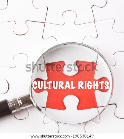 Concept image of missing jigsaw puzzle pieces found by magnifying glass revealing the CULTURAL RIGHTS words. - stock photo