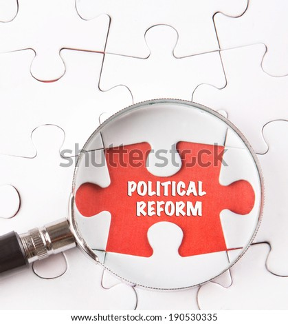 Concept image of missing jigsaw puzzle pieces found by magnifying glass revealing the POLITICAL REFORM words. - stock photo