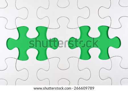 Concept image of missing puzzle pieces with green blank spaces