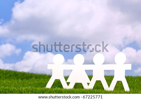 Concept image of paper people holding hands in a field with a blue sky background. - stock photo
