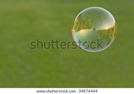 concept image of recession in economy; distinct reflection of house at sunset in a soap bubble on the green blurry background
