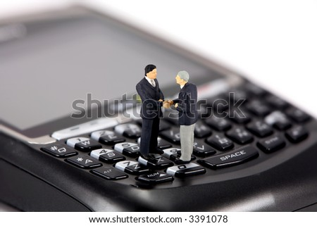 Concept image of two miniature businessmen shaking hands while standing on the keys of a cellphone with a qwerty keyboard. - stock photo