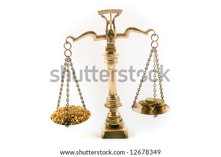 concept image of wheat grains and coins on scales to illustrate the value of food - stock photo