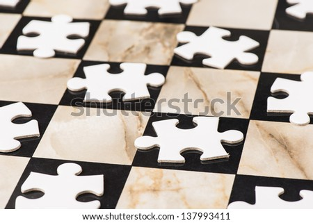 Concept image of white puzzle pieces on chess board - stock photo