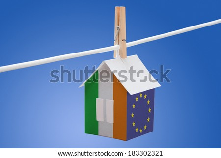 concept - Ireland and EU flag painted on a paper house hanging on a rope - stock photo
