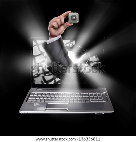 CONCEPT. laptop with broken screen and hand hand holds the processor CPU isolated on black background High resolution
