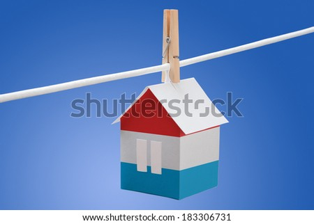 concept - Luxembourg flag painted on a paper house hanging on a rope - stock photo