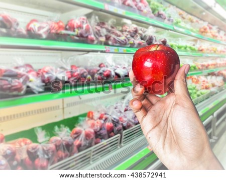 Concept, Man hand hold and choosing apple at fruits store in the supermarket background. - stock photo