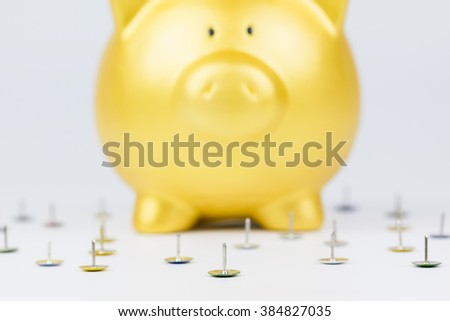 "concept : ""money protection"" many pins around gold piggy bank for protection - stock photo"