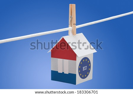 concept - Netherlands, dutch and EU flag painted on a paper house hanging on a rope - stock photo