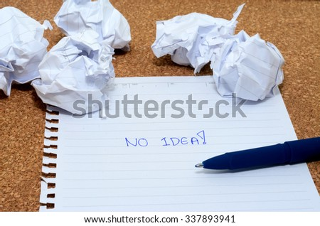 Concept - no idea , word on note paper and blue pen on wooden table with crumpled papers around - stock photo