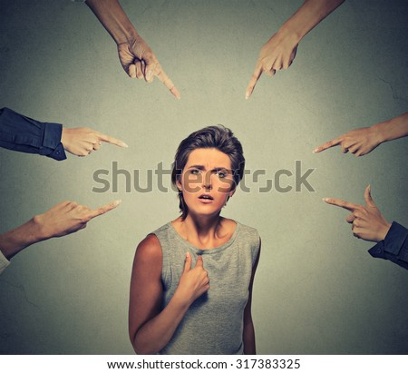 Concept of accusation guilty person girl. Upset angry looking woman asking me? many fingers pointing at her isolated on grey office wall background. Human face expression emotion feeling reaction - stock photo