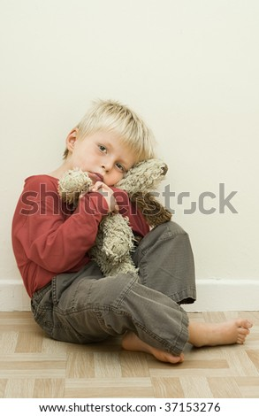 Concept of an unhappy toddler with his comfort toy. (desaturated) - stock photo