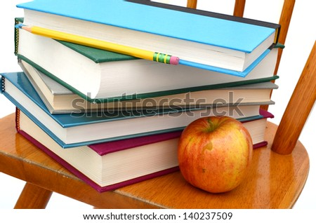 Concept of back to school: chair, apple and books - stock photo
