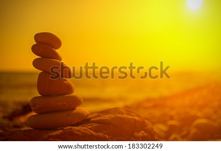 concept of balance and harmony. rocks on the coast of the Sea at sunset in the nature - stock photo