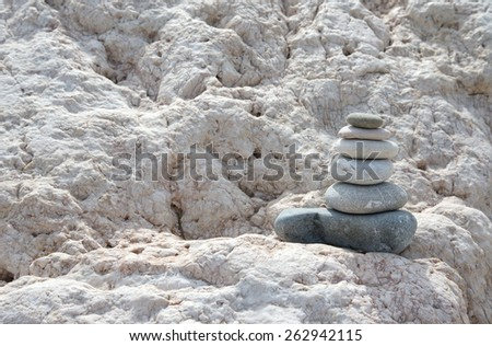 concept of balance and harmony. stacked stones pyramid on a marble rock. - stock photo
