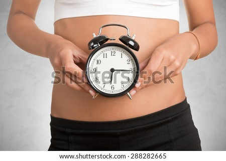 Concept of biological clock. Woman holding clock in front of her belly, isolated in white - stock photo