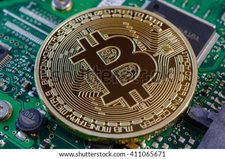 Concept of Bitcoin like a computer chip on motherboard. - stock photo