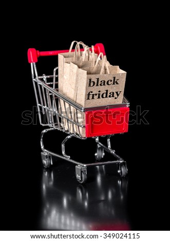 concept of black friday shopping cart with paper bags is isolated on black background - stock photo