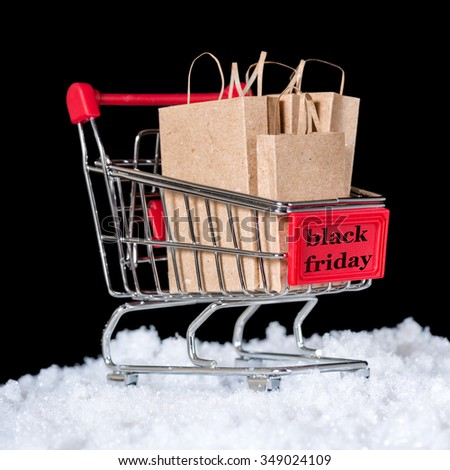 concept of black friday shopping trolley with paper bags in snow is isolated on black background - stock photo