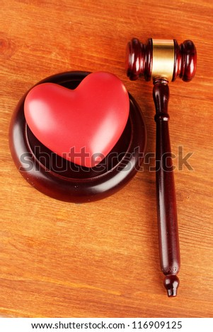 concept of broken heart because of divorce, on wooden background - stock photo