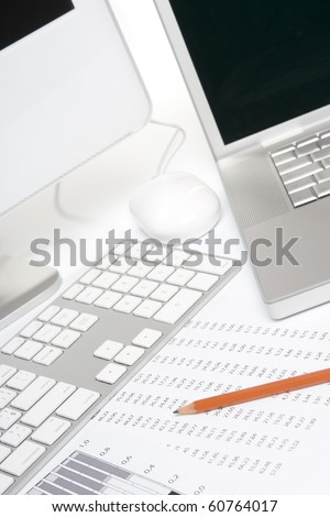 Concept of business analysis - sheet with numbers, graph, pencil and computers - stock photo