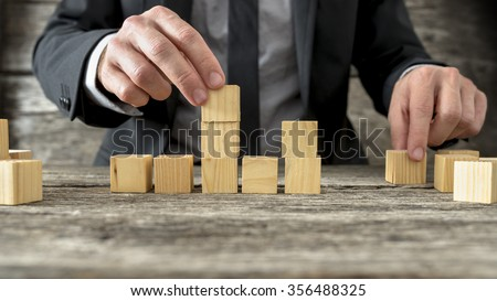 Concept of business strategy and planning - front view of male hand placing and positioning wooden blocks in various structures. - stock photo