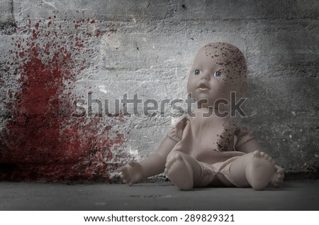 Concept of child abuse - Bloody doll, vintage - stock photo