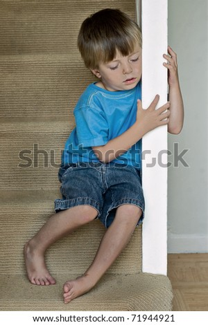 Concept of Child Abuse: Lonely boy sits on the stairs.