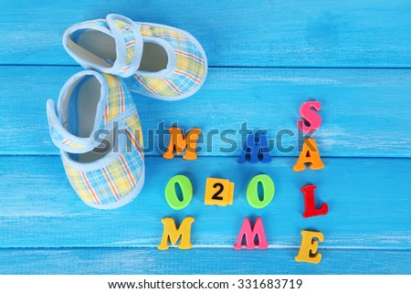 Concept of childish goods sale  on blue wooden background - stock photo
