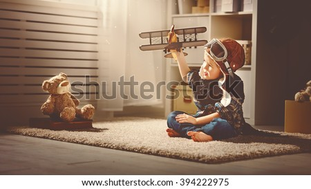 concept of children's dreams and travels.  pilot aviator child with a toy airplane plays at home in his room - stock photo