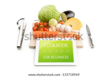 Concept of cookbook for beginners on the tablet computer. Near the tablet computer is a cutting board, cutlery and food. Isolated on white. - stock photo