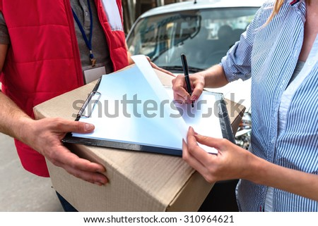Concept of courier delivers package for woman - stock photo