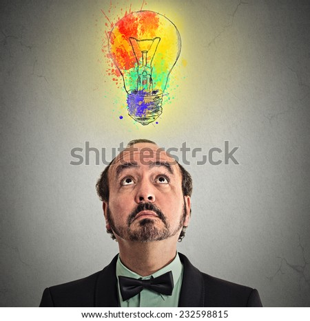 Concept of Creative business idea with colorful lightbulb. Portrait middle aged businessman came up with solution answer for problem looking up isolated on grey wall background. Perception vision  - stock photo