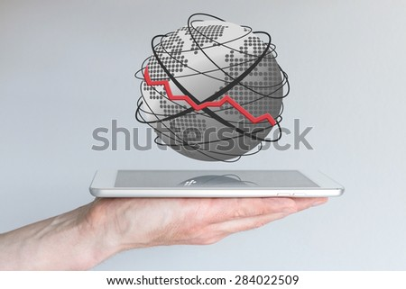 Concept of decline within mobile computing. Shrinking sales, e.g. for smart phones, tablets or other mobile devices. Hand holding tablet with globe.