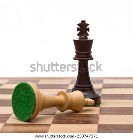 Concept of defeat (white king defeated by black, camera focus on black king) - stock photo
