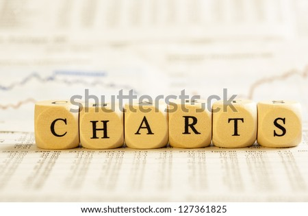 Concept of dices with letters forming word: Charts. On generic newspaper background with stock market numbers and some blurred charts. Dices made from wood with natural imperfections.
