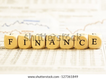 Concept of dices with letters forming word: Finance. On generic newspaper background with stock market numbers and some blurred charts.  Dices made from wood with natural imperfections