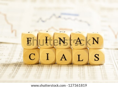 Concept of dices with letters forming word: Financials. On generic newspaper background with stock market numbers and some blurred charts.  Dices made from wood with natural imperfections.