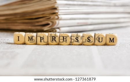 Concept of dices with letters forming word: Impressum (German for Imprint). Generic newspaper background with some blurred text on the bottom and paper stack in the back. - stock photo