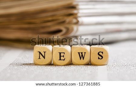 Concept of dices with letters forming word: News. Generic newspaper background with some blurred text on the bottom and paper stack in the back. Dices made from wood with natural imperfections. - stock photo