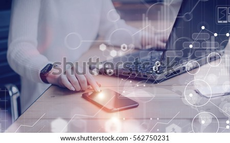 Concept of digital screen,virtual connection icon,diagram,graph interfaces.Pensive young beautiful businesswoman using modern mobile phone and laptop while sitting at her working place.Flares
