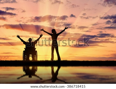Concept of disability and disease. Silhouette happy disabled person in a wheelchair next to the guardian at sunset