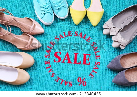 Concept of discount. Female fashion shoes on blue carpet - stock photo